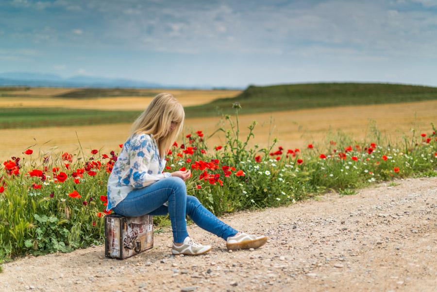 フリー写真 田舎道でトランクの上に座っている外国人女性