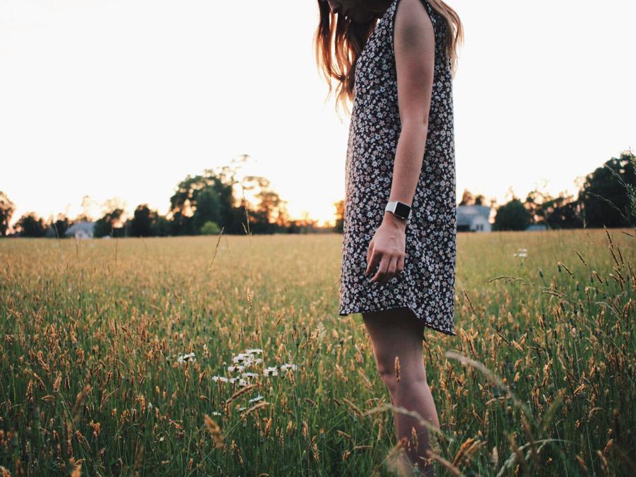 フリー写真 牧草地の中で花を見つける女性