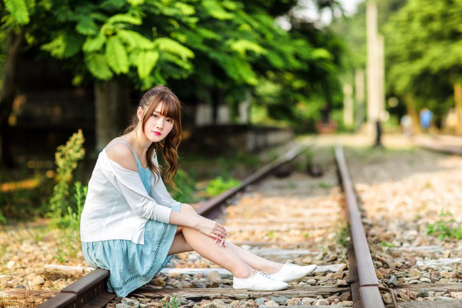 フリー写真 線路の上に腰掛ける女性