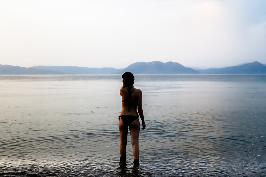 フリー写真 水着姿で浅瀬に立つ女性の後ろ姿