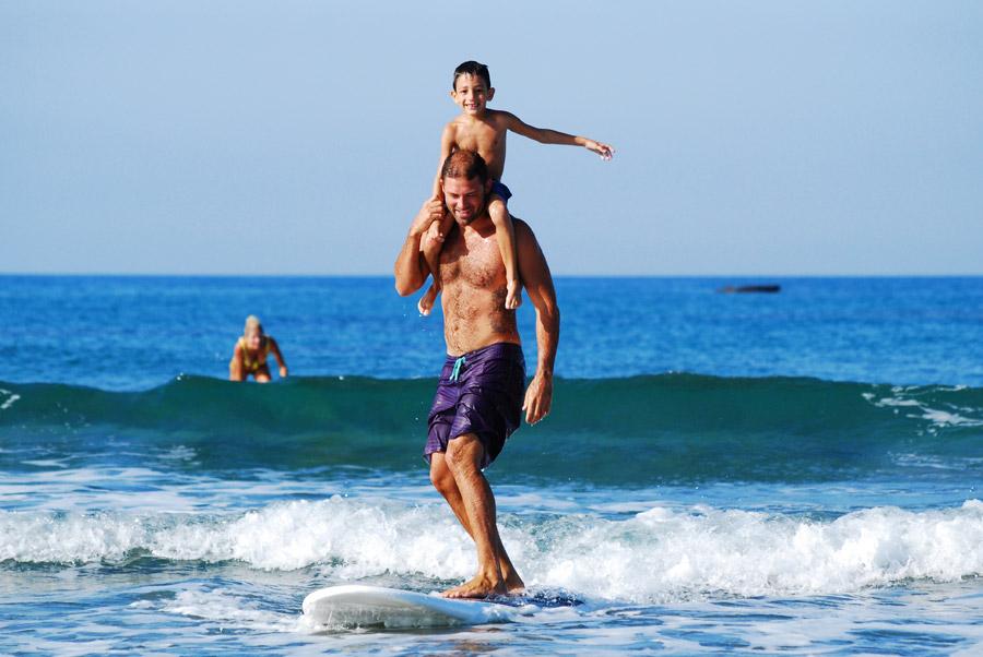 フリー写真 肩車してサーフィンする親子