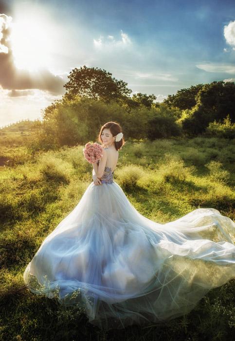 フリー写真 草むらでウェディングドレス姿でブーケを持つ新婦