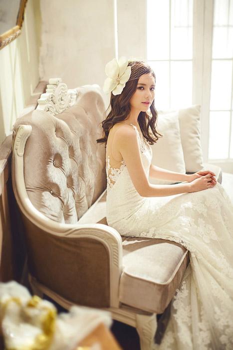 フリー写真 ウェディングドレスを着てソファーに座る新婦