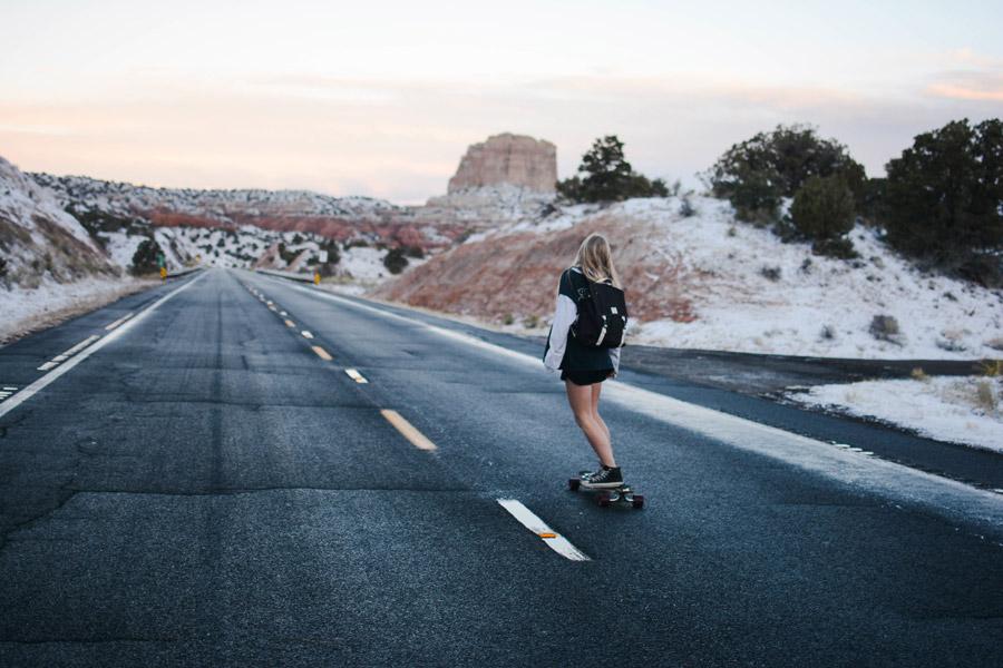 フリー写真 雪の残る荒野とスケボーに乗る女性の後ろ姿