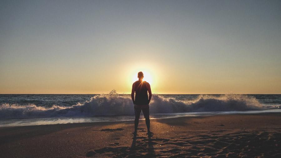 フリー写真 波しぶきと夕暮れのビーチに立つ男性