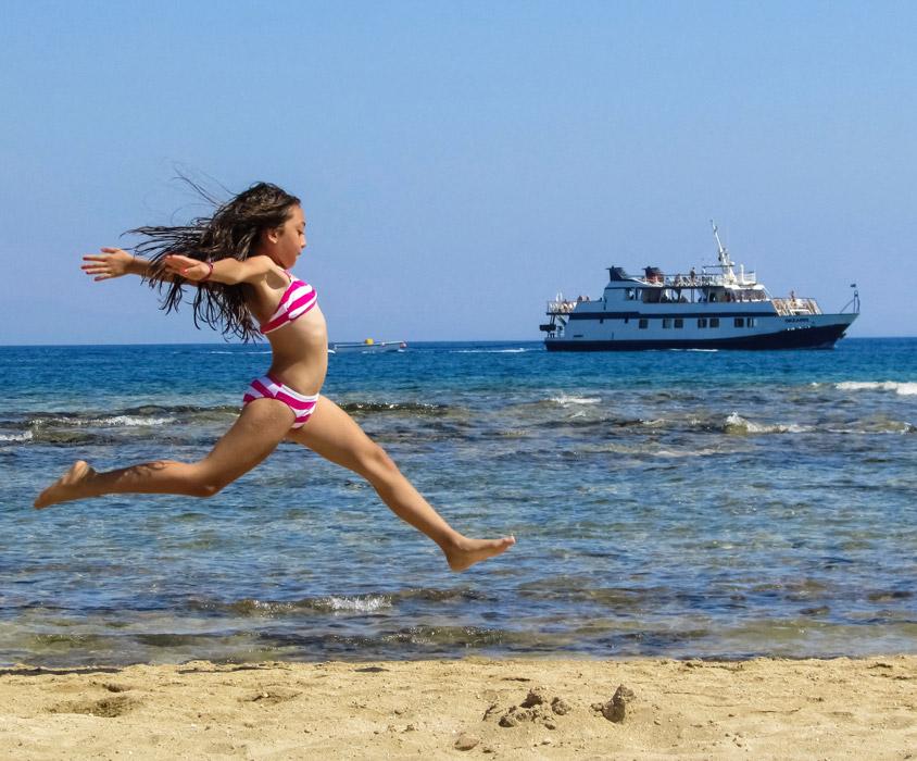 フリー写真 水着姿で跳びはねる女の子と船