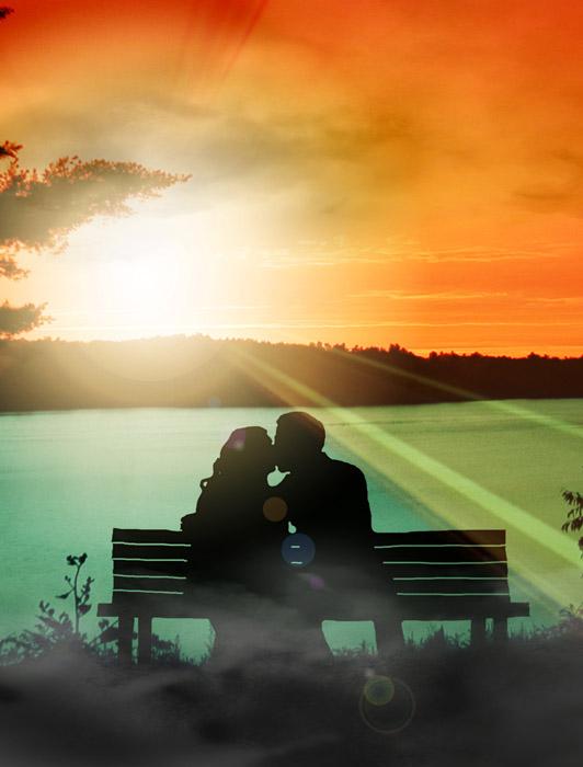 フリー写真 夕日とベンチでキスをするカップルのシルエット