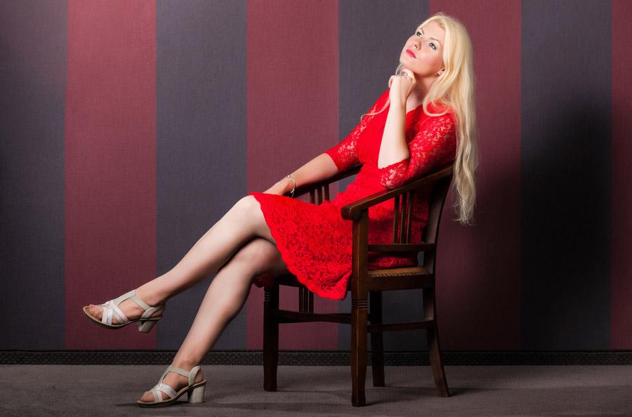 フリー写真 椅子に座って思いを巡らす金髪の外国人女性