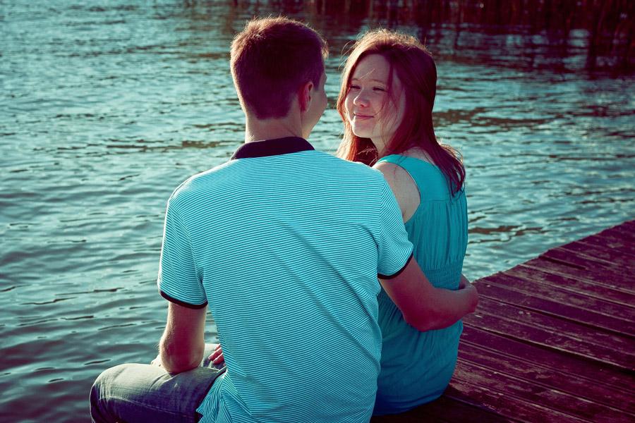 フリー写真 桟橋の上に座って見つめ合うカップル