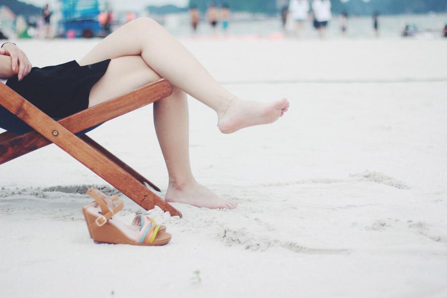 フリー写真 砂浜でデッキチェアに座る女性の足