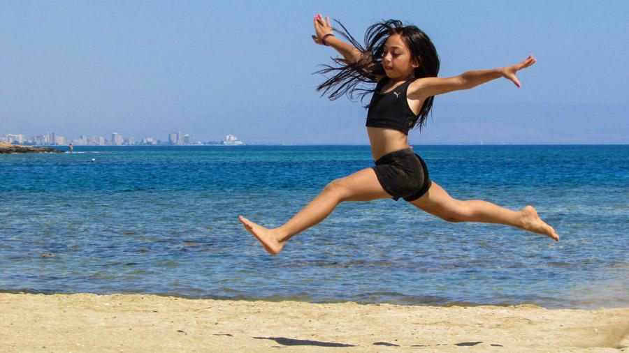フリー写真 砂浜をジャンプする女の子