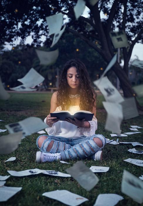 フリー写真 読書している女性と光る本とバラまかれたページ