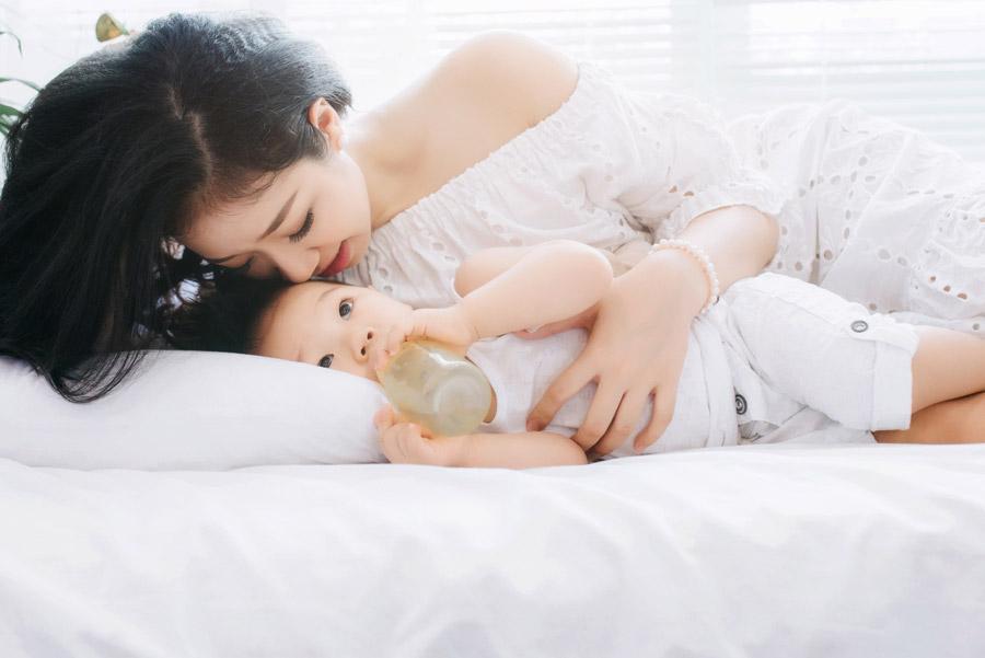 フリー写真 哺乳瓶を咥えながらママを見ている赤ちゃん