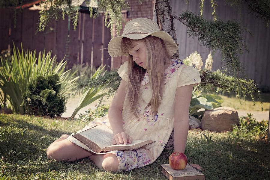 フリー写真 芝生の上で横座りして読書中の外国の女の子