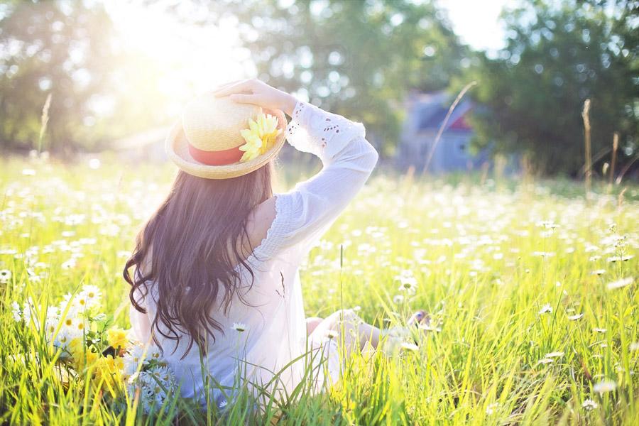フリー写真 草花の上に座る女性の後ろ姿