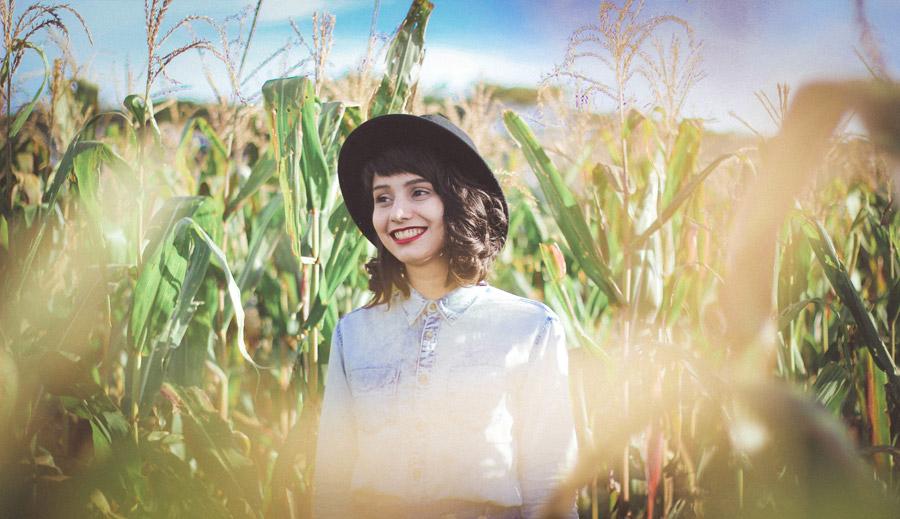フリー写真 とうもろこし畑にいる帽子を被った外国人女性