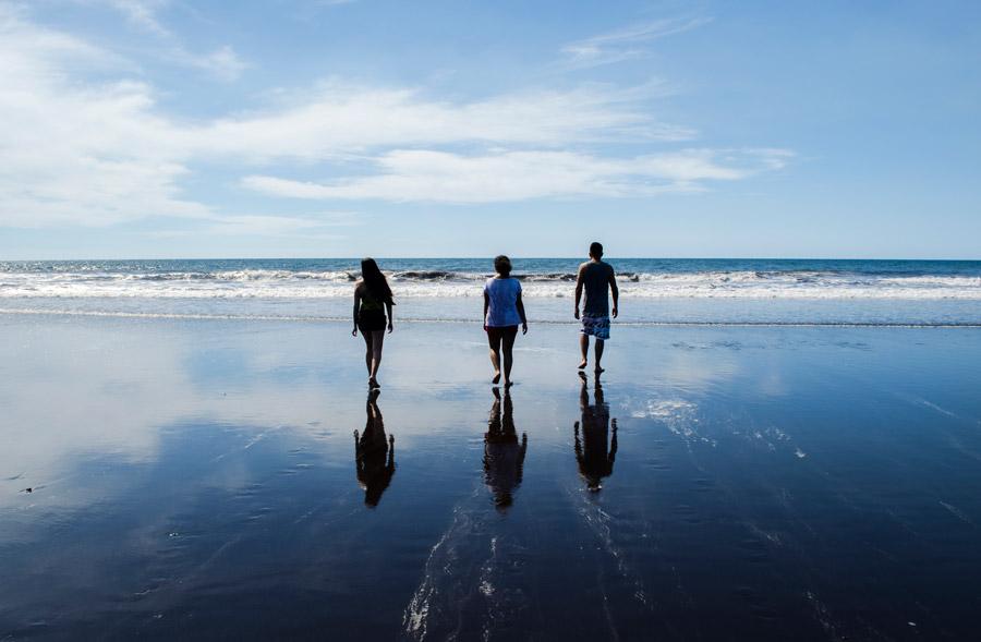 フリー写真 海に向かう三人の人物の後ろ姿