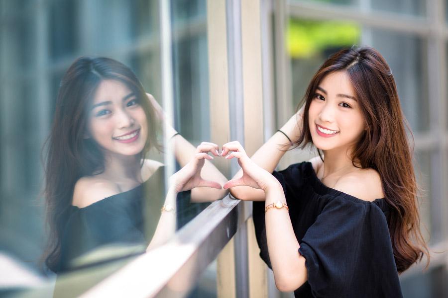 フリー写真 窓に映る自分と手でハートを作る女性