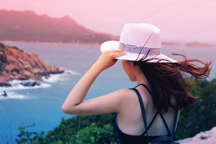 フリー写真 手で帽子を押さえながら海を眺める女性