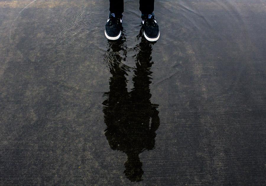 フリー写真 足と水たまりに映る人物の影