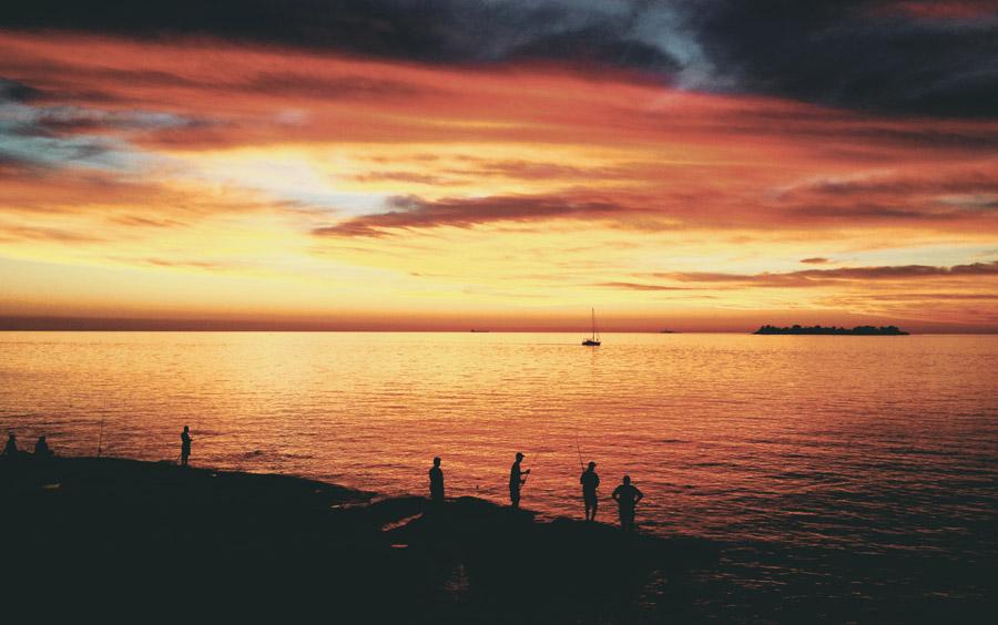 フリー写真 夕暮れの海岸で釣りをする人々