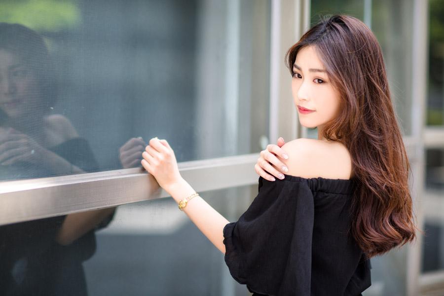 フリー写真 オフショのブラウス姿で窓の前に立つ女性