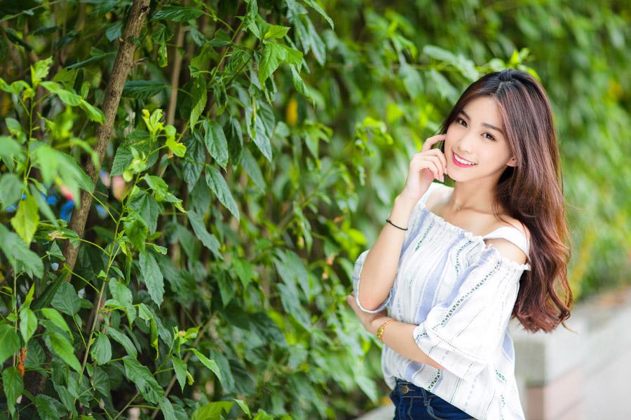 フリー写真 植物の前で頬と顎に指を当てる女性