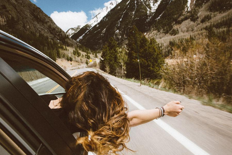 フリー写真 車の窓から手と頭を出す女性の後ろ姿