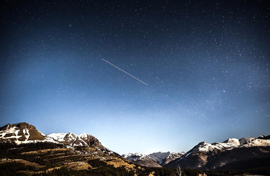 フリー写真 山と星空を横切る流れ星の風景