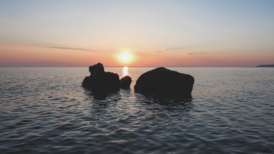フリー写真 海に浮かぶ岩と夕日の風景