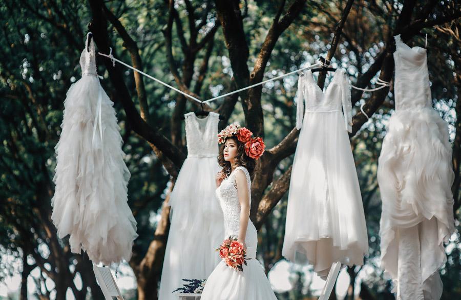 フリー写真 木に吊り下げられたウェディングドレスと女性