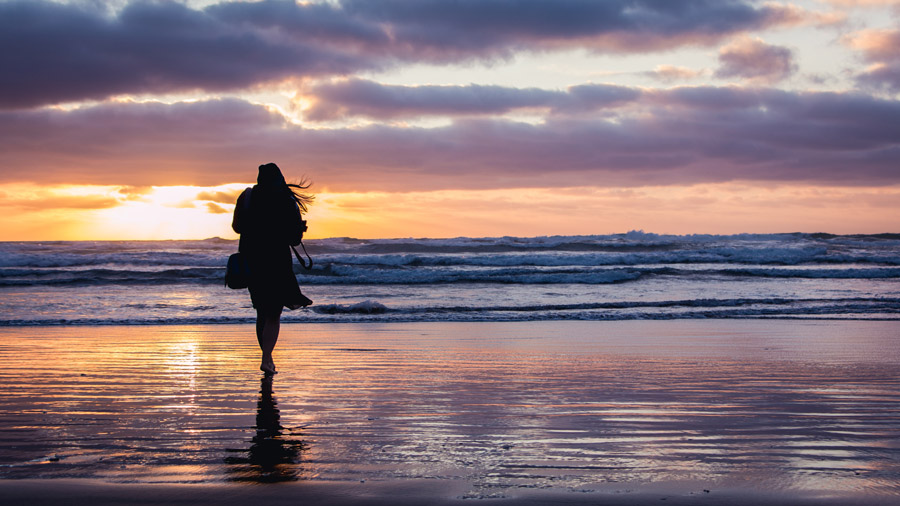 フリー写真 夕暮れの浜辺に立つ女性のシルエット