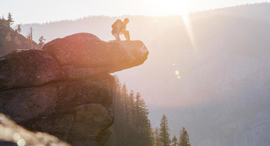フリー写真 オーバーハンギング・ロックから崖の下を見る男性