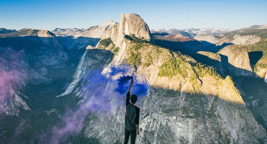 フリー写真 ヨセミテ渓谷と発煙筒を持つ男性の後ろ姿