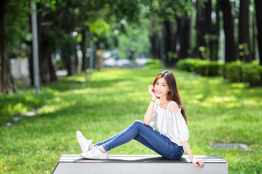 フリー写真 ベンチの上に座って頬杖をつく女性