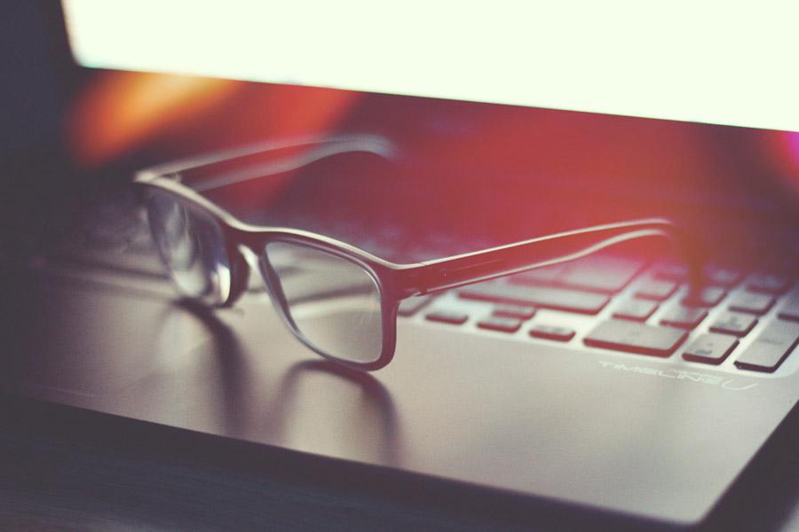 フリー写真 ノートパソコンの上に置かれた眼鏡