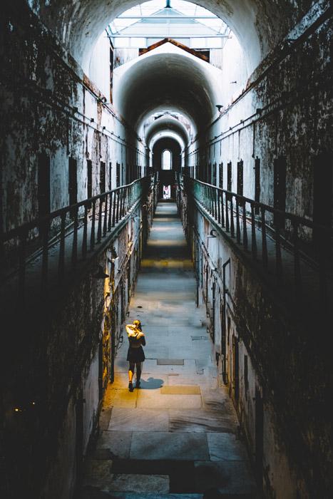 フリー写真 廃墟となったイースタン州立刑務所の廊下を歩く女性