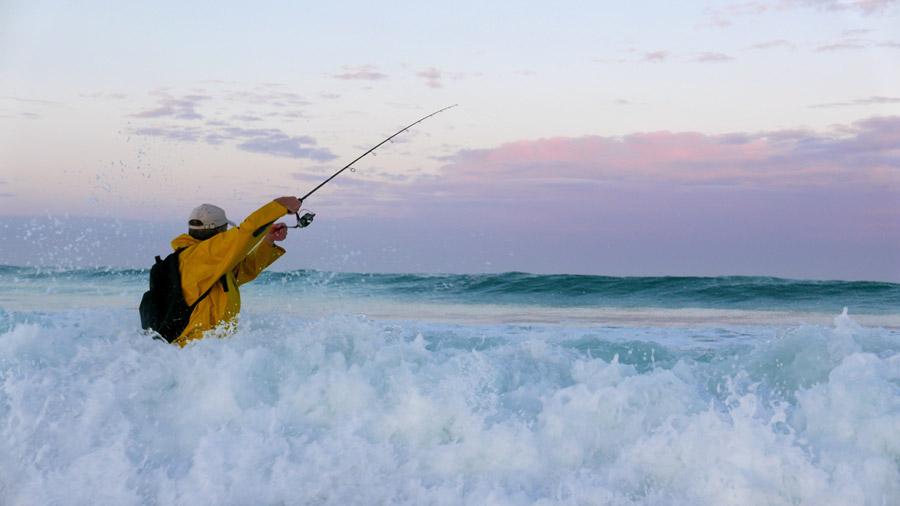 フリー写真 海に入って魚を釣る釣り人