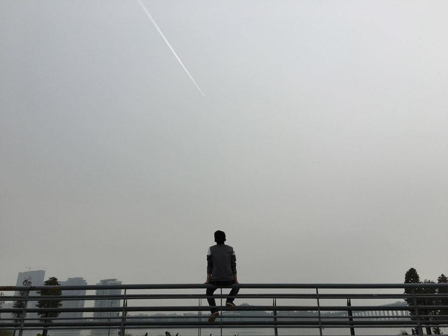 フリー写真 フェンスに腰掛けて飛行機雲を眺める男性