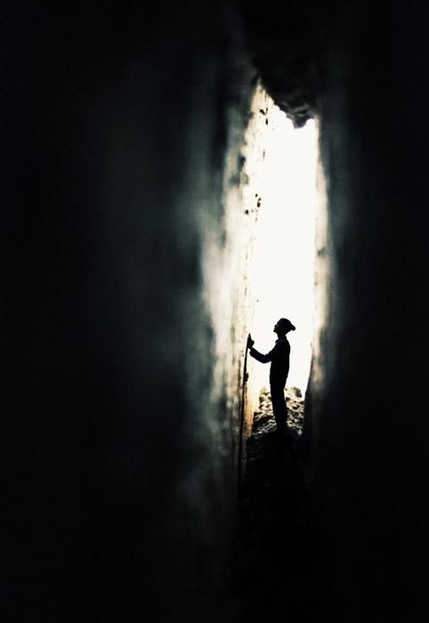 フリー写真 狭い壁の隙間にいる人物のシルエット