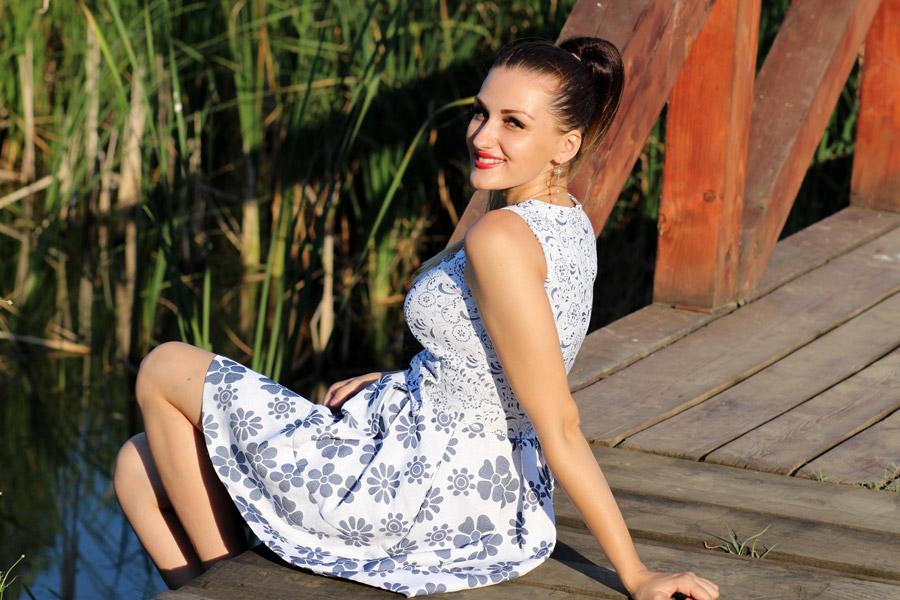 フリー写真 ワンピース姿で橋の上に座る外国人女性