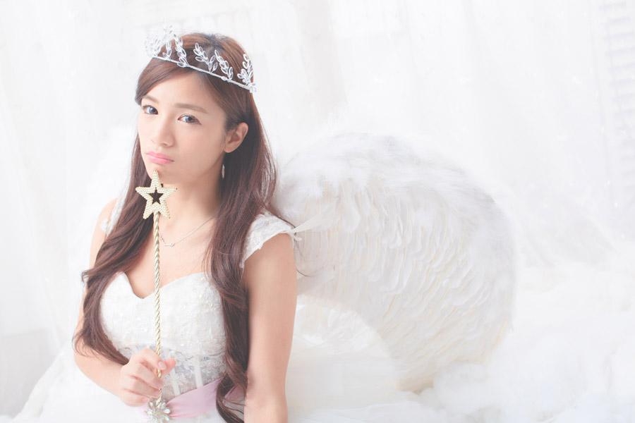 フリー写真 魔法の杖を顎に当てる天使姿の女性