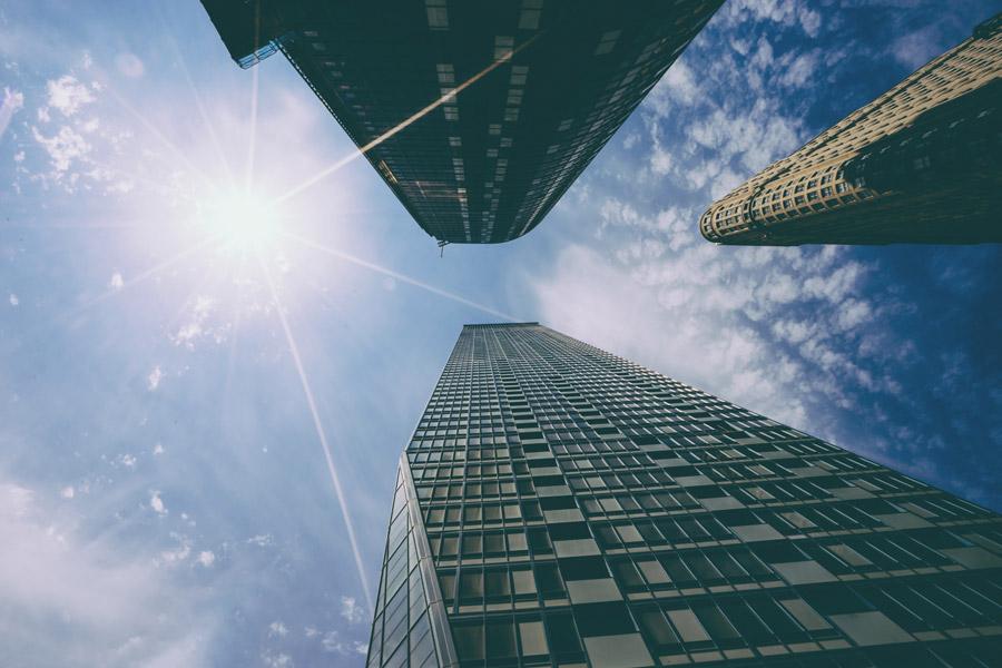 フリー写真 下から見上げるニューヨークの高層ビルと太陽の光