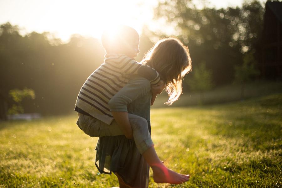 フリー写真 太陽の光と弟をおんぶする姉