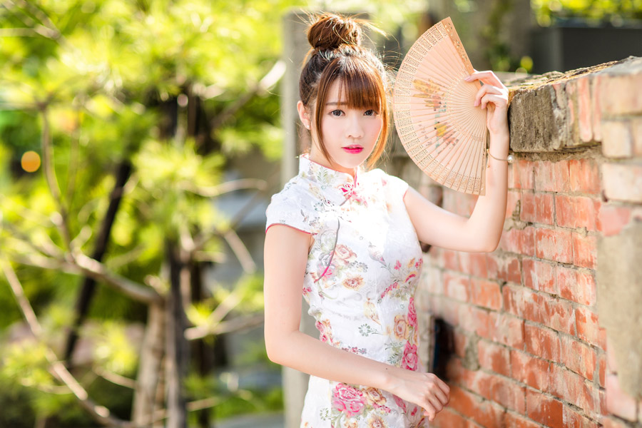 フリー写真 チャイナドレス姿で扇子を広げる女性