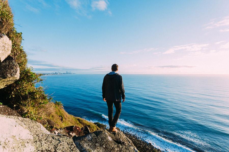 フリー写真 海の向こうの街を眺める男性の後ろ姿