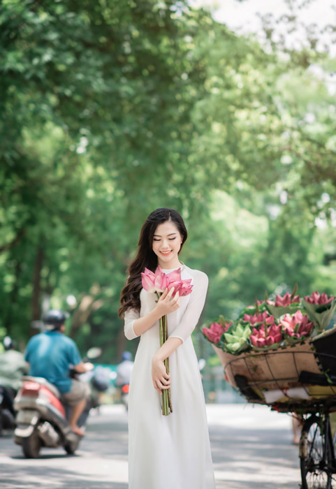 フリー写真 アオザイ姿で露店で買った蓮を抱きしめる女性