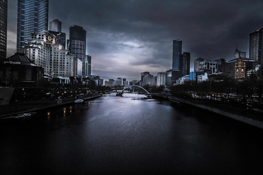 フリー写真 暗雲に覆われた川と都市の風景