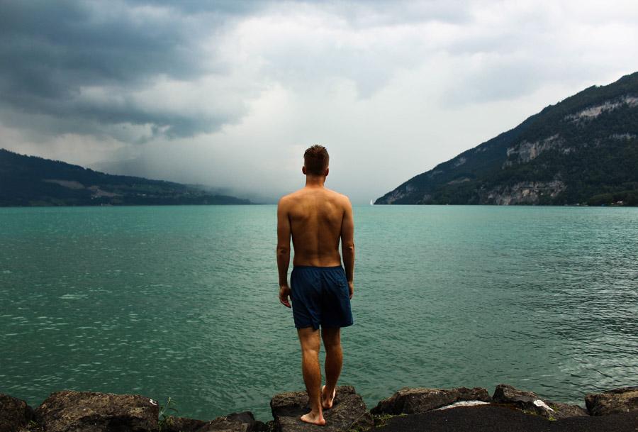 フリー写真 湖の前に立つ海パン姿の男性の後ろ姿