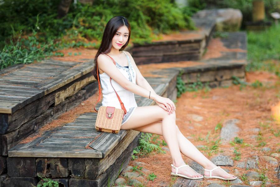 フリー写真 キャミワンピとサンダル姿でベンチに腰掛ける女性